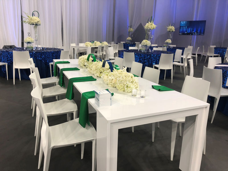 An indoor banquet setup with white table and flowers, blue sparkly tablecloths and green accents